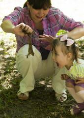 Мама поймала и показывает живую лягушку двухлетней дочке