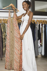 African woman holding dress in clothing store