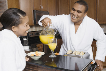 African man pouring orange juice for wife
