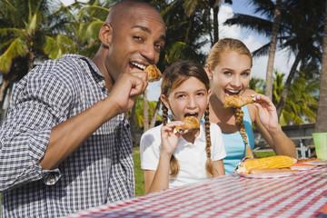 Mixed Race family eating at picnic table