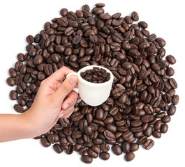Cup of coffee beans on coffee beans background