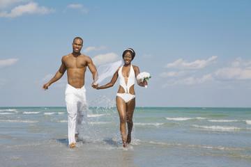 African bride and groom running in ocean surf