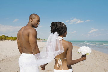African bride and groom holding hands at beach