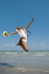 African bride jumping in ocean surf