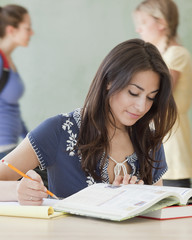 Hispanic woman studying in classroom