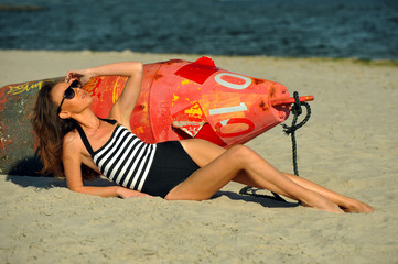 Beautiful swimsuit model posing at the beach with the bouy.