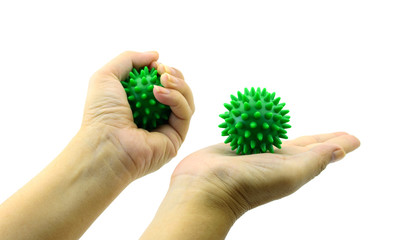 hand with Spiny plastic green massage ball isolated on white