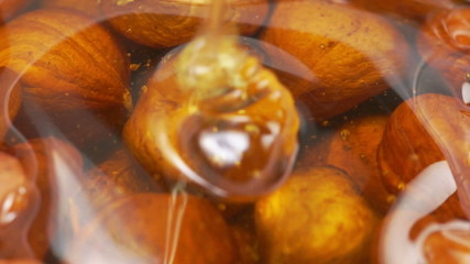 Honey pouring into bowl of hazelnuts in slow motion.