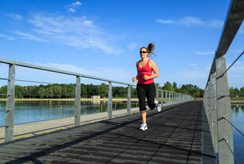 Woman running on a boardwalk at a lake.