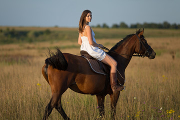 Girl in white dress riding on a horse