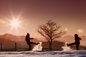 silhouette of people playing with snow on sunrise