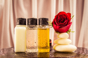 Spa setting with red rose on white stone and aroma oil bottles o