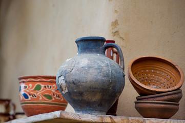 Traditional ceramic handmade jugs on a wooden shelf