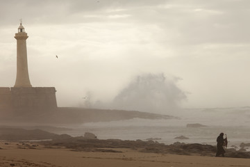 Lighthouse on the cliff with fortifications in Rabat with storm