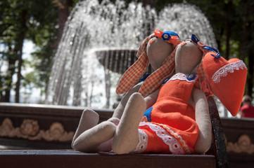 Игрушки зайцы на фоне фонтана