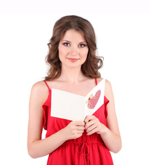 Beautiful young girl in red dress with card isolated on white