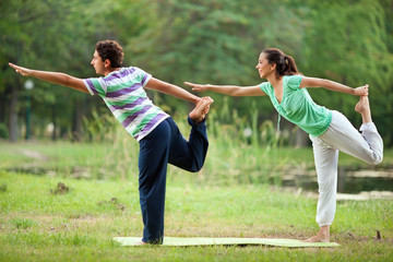 Couple practising yoga in park
