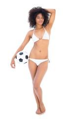Beautiful fit girl in white bikini holding football