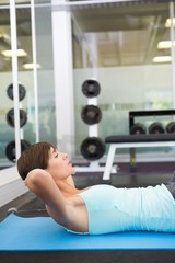 Fit brunette doing sit up on exercise mat