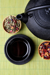 Black teapot, bowl and tea on bamboo mat background