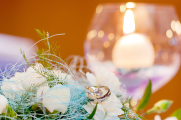 Wedding rings lying on white kytce a candle in a glass cup