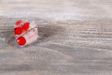 Ice cube with red currant, on wooden background