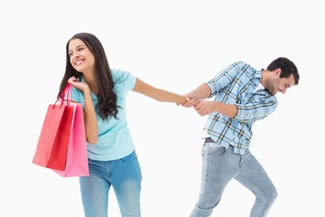Attractive young man pulling his shopaholic girlfriend