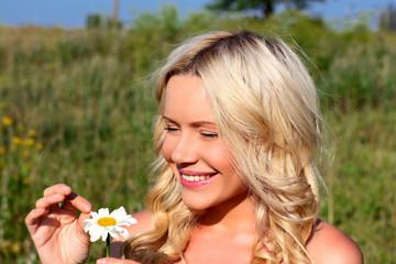 Красивая девушка блондинка гадает на ромашке