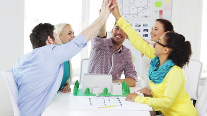 smiling architects doing high five in office