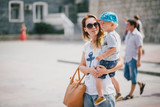 Young fashion mother and her son walking outdoors in city