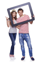 Happy couple looking through tablet frame