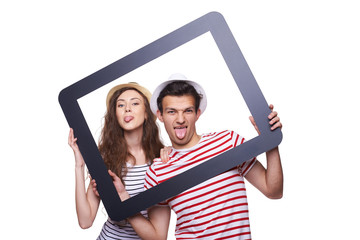 Happy couple showing tongue through tablet frame