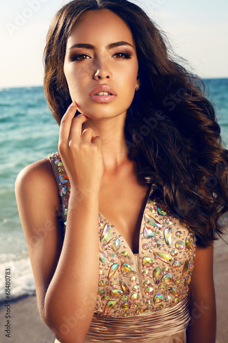 beautiful girl with dark hair in luxurious dress posing on beach - 68480783
