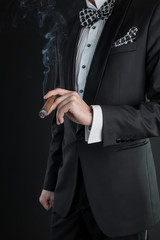 Man in a black suit holding a cigar in a left hand