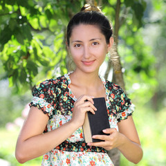 beautiful woman of Asian appearance is reading a book outdoors