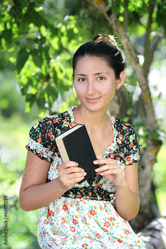 canvas print picture beautiful woman of Asian appearance is reading a book outdoors