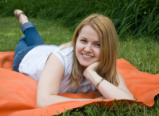 Attractive young woman lying in green grass
