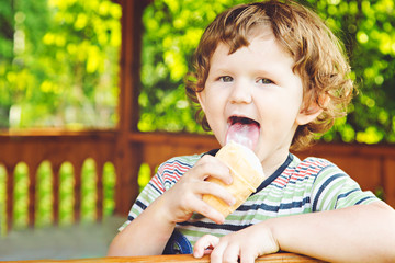Happy child eating ice-cream in summer park.
