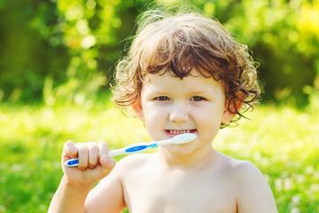 Little boy brushing her teeth
