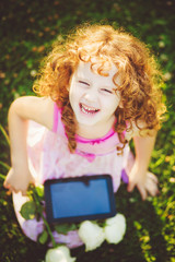 Little girl sitting on grass and hold white flowers and tablet p