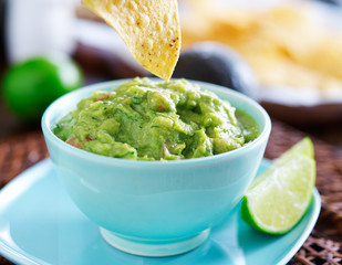 eating guacamole with tortilla chip from bowl