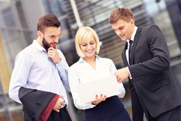 Group of business people standing outside modern building with c