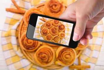 Hands taking photo  cinnamon rolls with smartphone