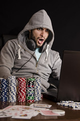 Shocked poker player in front of a laptop