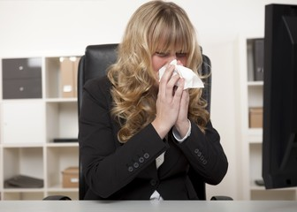 Young businesswoman blowing her nose