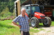 Proud farmer standing in front of his red tractor