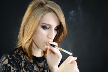 Frau zündet Zigarette mit Feuerzeug an