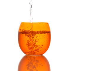 Water poured into beautiful orange colour glass - splashes.