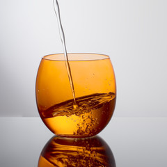 Water pouring into orange colour glass. Unusual angle.
