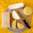 Assorted cheeses on old wooden board, farm produce
